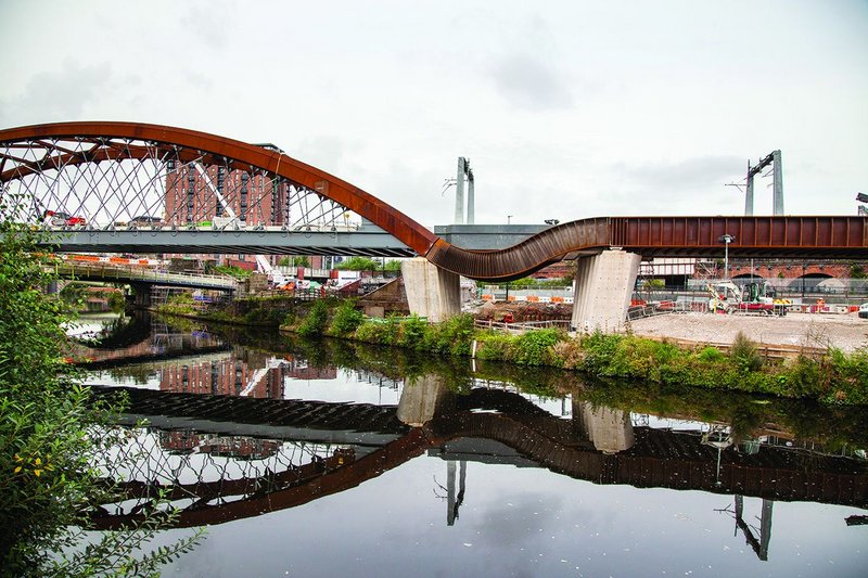 The cascade form enables a seamless transition between the river and the road bridge.
