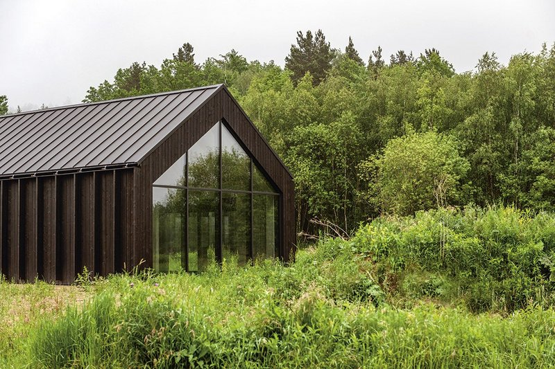 Through reflection, largely glazed gable ends help nestle the decidedly black home and studio in the surrounding landscape.