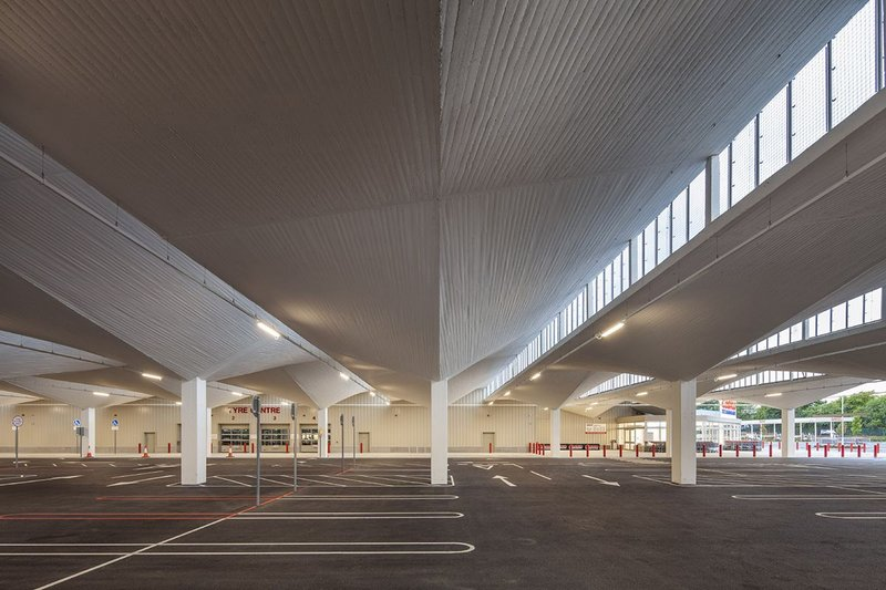 The rhythm of hyper shells and clerestory windows give newly painted concrete glory to the car park below.
