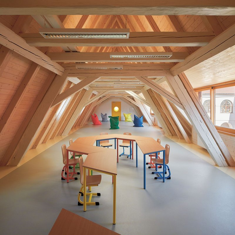 Multi-purpose teaching space with an attic feel and marmoleum floor.