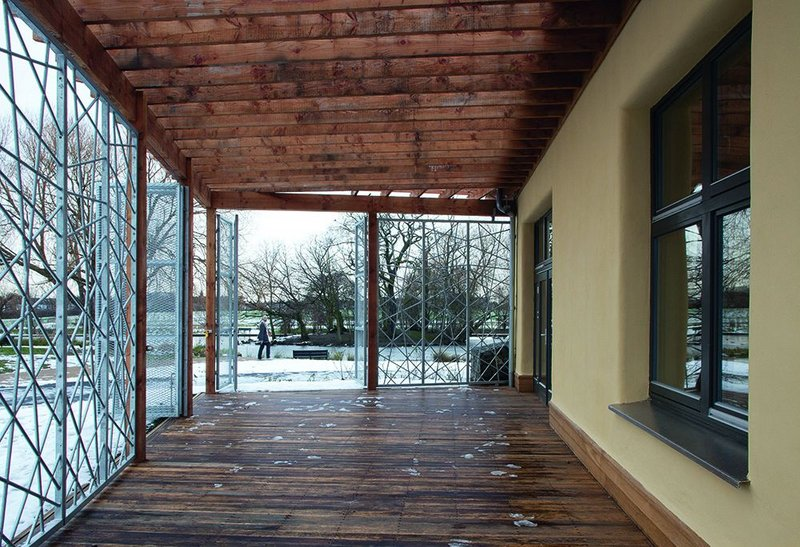 The café terrace, looking south. Galvanised grilles not only make the Eco-Hub more secure, they suggest the branches of the trees beyond