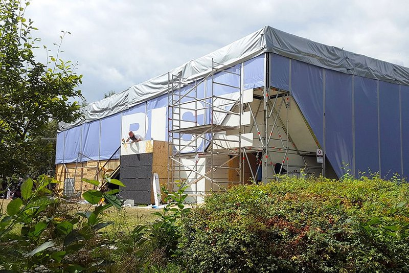 Scaffolding is clad in tensioned tarpaulin.