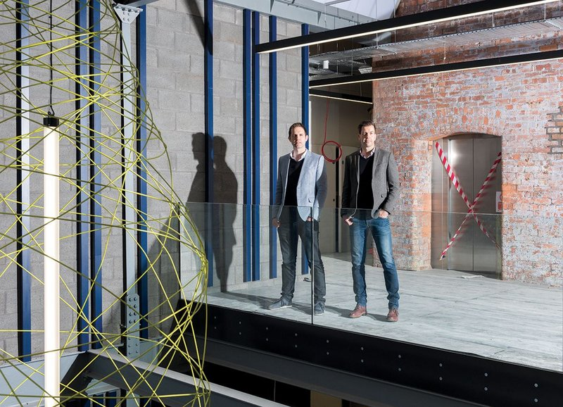 Nick Moss (left) and Andrew Edmunds on the atrium of their refurbishment project Stubbs Mills in New Islington, Manchester. The bobbin inspired lamp hangs to the left.