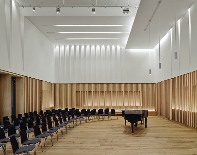 The acoustic treatment of the surfaces in the rehearsal/recital room is thoroughly architectural. Movable thick felt drapes lie behind the timber panelling.