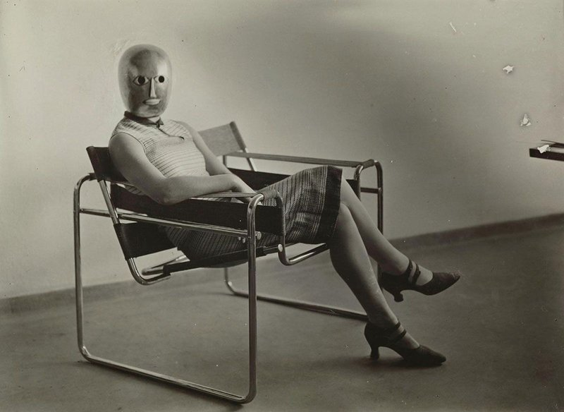 Woman on club chair B3 by Marcel Breuer, mask by Oskar Schlemmer, dress by Lis Beyer.