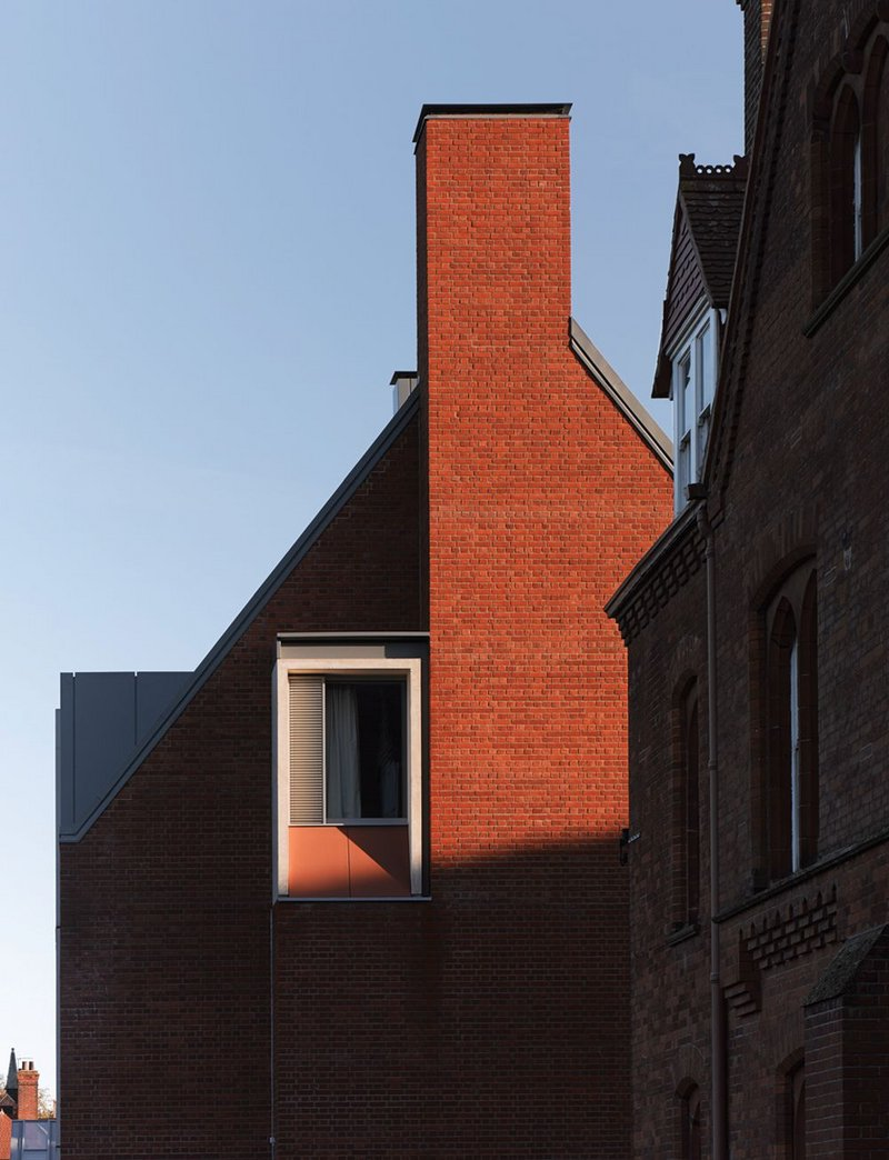 Gable end. Concrete frames the window ensemble and terracotta cladding.
