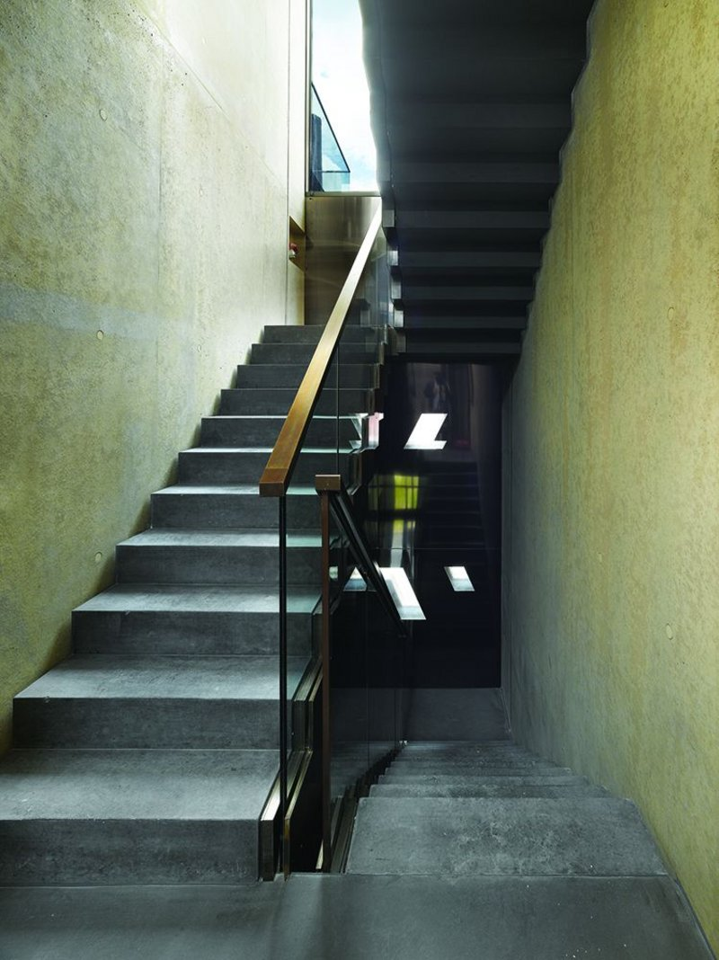 The monolithic theme set on the outside continues internally; the staircase detailing in concrete, glass and brass  alludes to Scarpa