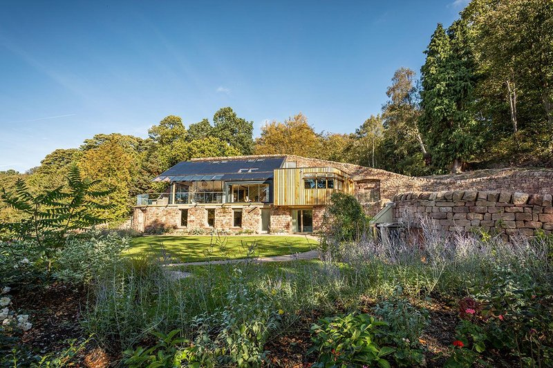 Quarry Stones House is visually conceived as a retaining wall with garden outbuildings – greenhouse and shed.