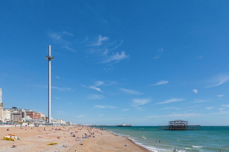 British Airways i360 with the ruins of West Pier to the right and Brighton Palace Pier beyond.
