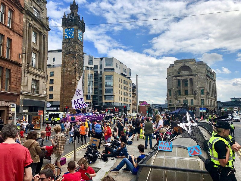 "Example of civil disobedience: Glasgow's Summer Uprising transformed the historic Trongate, carrying its message in both English and Scots Gaelic on the boat. For the Scottish and UK Governments to ""Act Now"", to treat the Climate Emergency like the emergency it is: to halt biodiversity loss and reduce greenhouse gas emissions to net zero by 2025; and ""The Future You Fear Is Already Here"": showing solidarity with climate refugees and those already suffering daily impacts of climate breakdown in the Global South and Indigenous North. July 2019."
