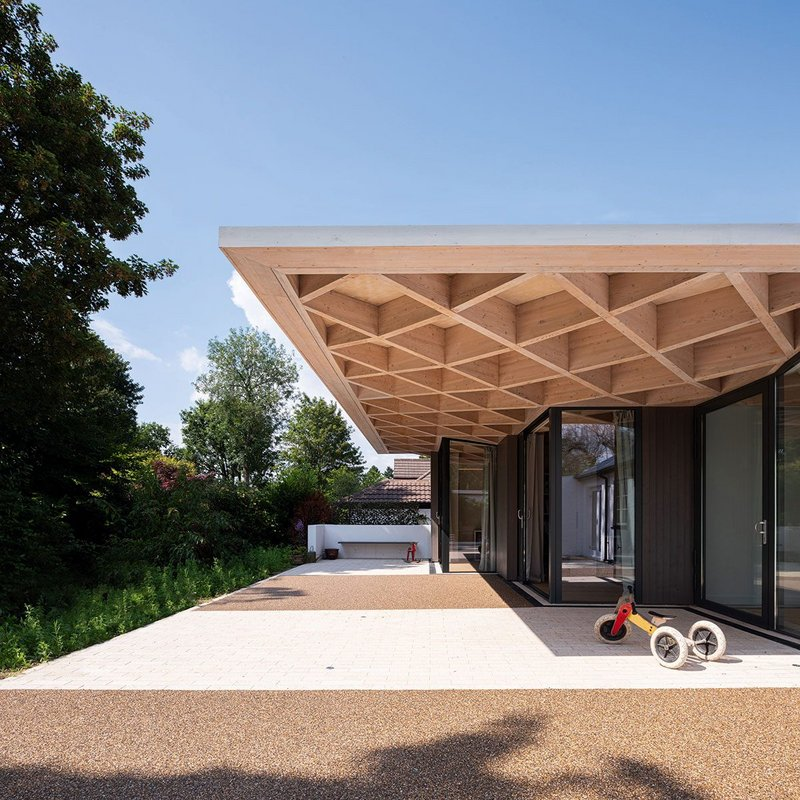 The rear elevation of the section shows the generosity of the cantilever of the timber diagrid roof, allowing the children space to play beneath it.