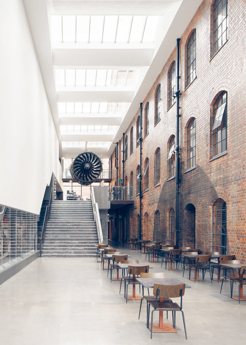 The Civic Hall or entrance atrium to the museum with a café and stairs rising to the museum shop and main exhibition galleries. A Rolls-Royce Trent jet engine dominates the space.