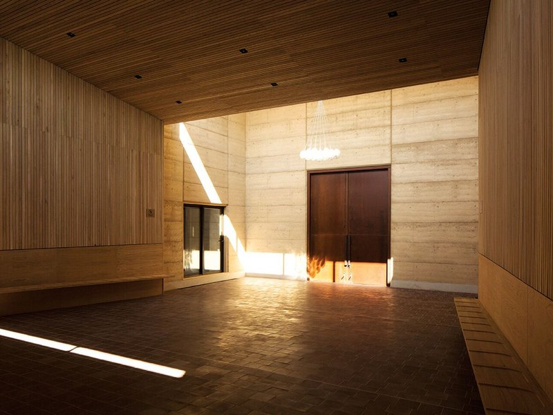 The rammed earth prayer halls lit by clerestory glazing which allows light to flood into the double-height space.