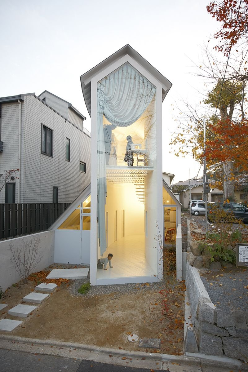 O House, Kyoto, 2009, designed by Hideyuki Nakayama. The 59.71m2 house consists of a gabled central block flanked by two adjacent structures containing the everyday facilities. First floor bedrooms are accessed by an external staircase from the garden.