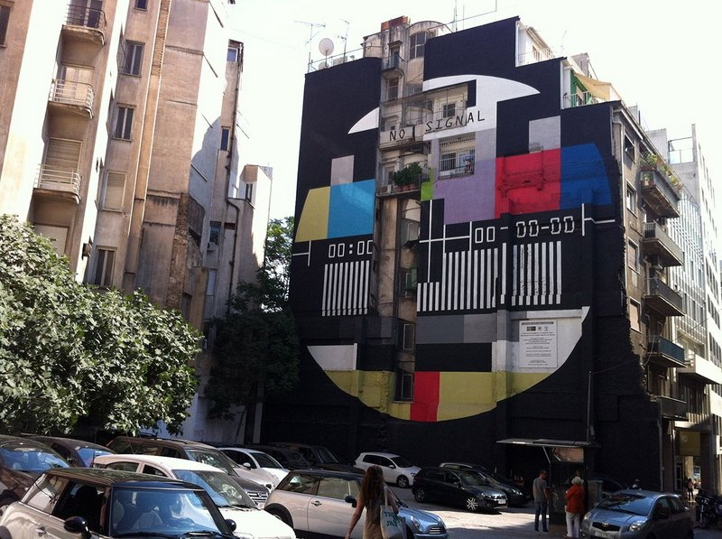 Polykatoikía registering protest.  The side wall of a polykatoikia in Athens, near Syntagma Square, painted with the old 'no signal' image from the national channel ERT, after it was forced to close, 2013.