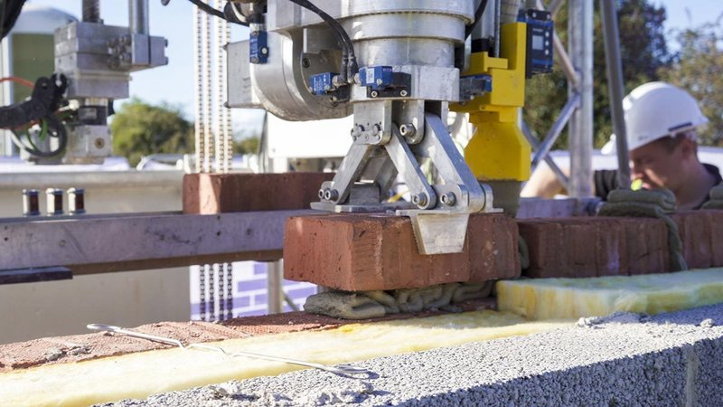 Sensors and sophisticated control software help the robot precisely align bricks of varying sizes.