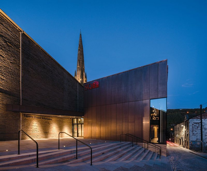 Square Chapel west entrance. Machined copper panels of the new auditorium counterpoint the blank freestone walls of the Piece Hall. The spire of the 1855 Square Chapel is behind.