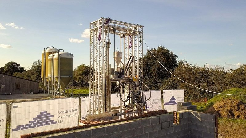 The robotic laying arm is mounted on a 9m high lift frame that moves along a track.