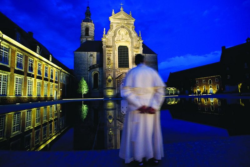 A monk contemplates the courtyard, which is transformed by the pool by night