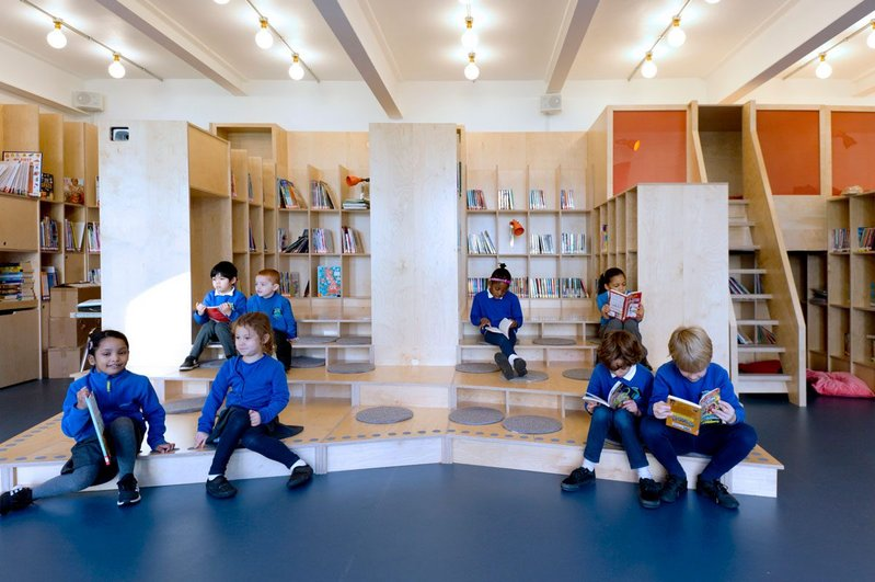 Steps form both a stage and an informal seating area in the new school library at Thornhill Primary School in London's Islington, designed by Jan Kattein Architects.