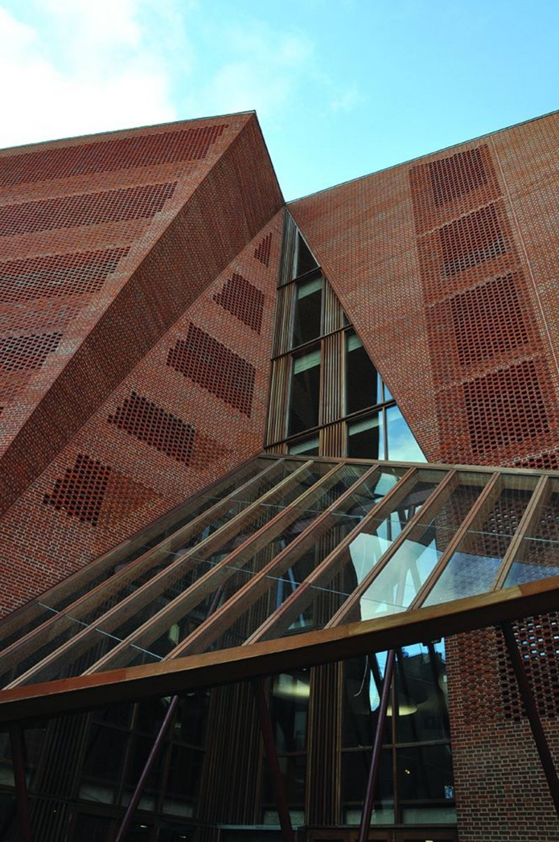 The building's folded facade expands into perforated openings with glazing set behind, plus areas of 'blind' textured brickwork. All in handmade brick.