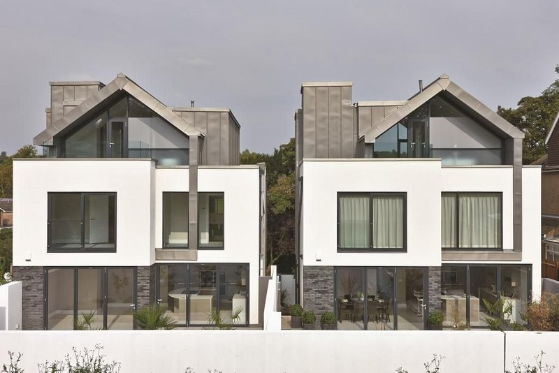 The twin houses are modern in aesthetic but have a crafted feel and suburban scale