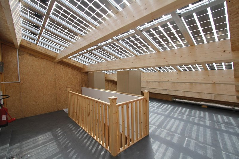 PV panels are integrated into the roof structure, allowing the space below to be naturally lit.