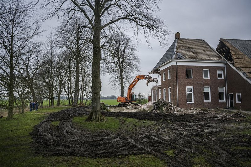 An unsalvageable farmhouse in the Groningen region being demolished because of safety concerns.