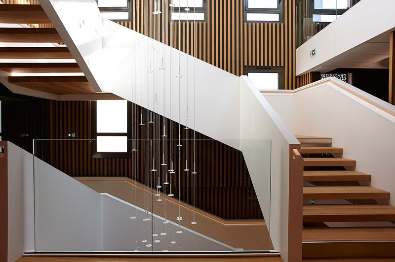 Staircase in oak and HI-MACS solid surface material at the CMMA building in Châlons-en-Champagne, France.