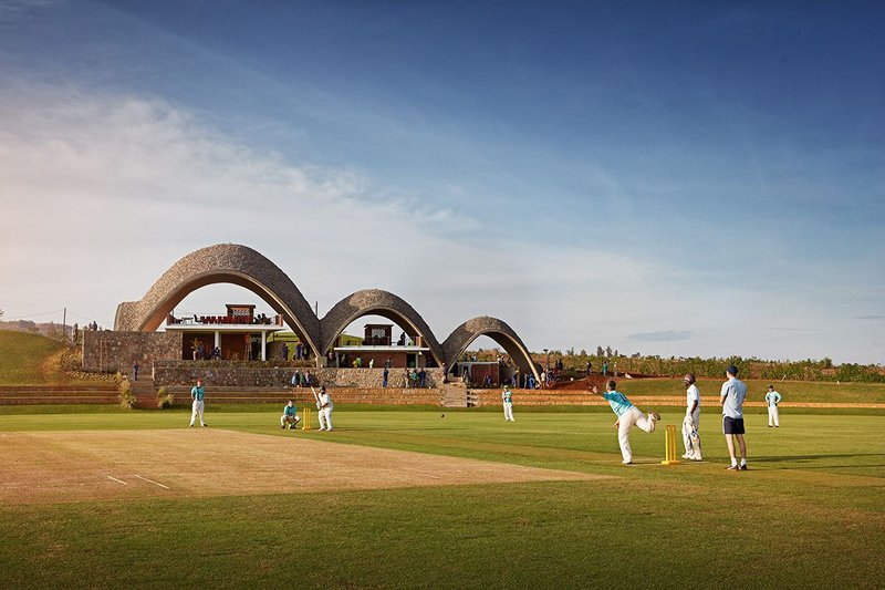 Team Yorkshire Tea playing at the Rwandan Cricket Stadium. The three tiled shells are open to the sides, with enclosed spaces only at the ground floor.