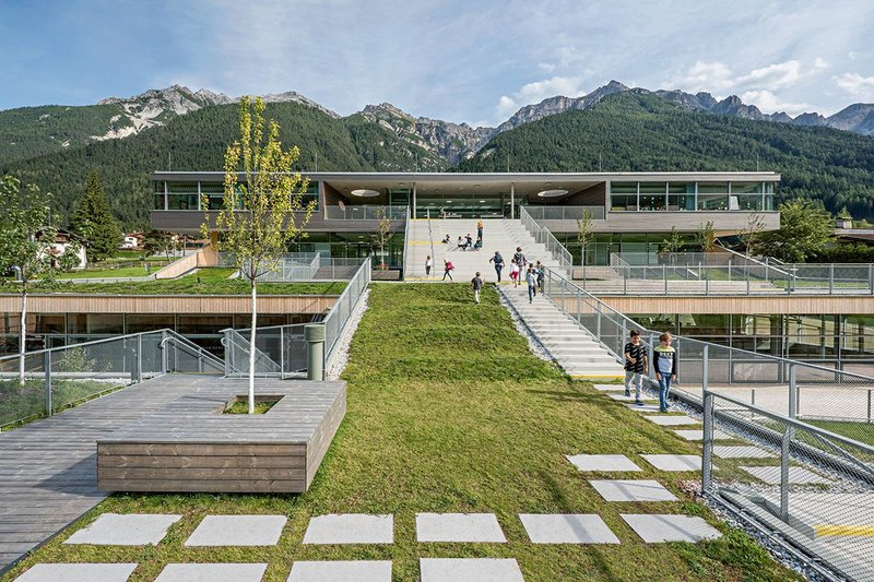 On the roofs of the school, one finds a terraced landscape with green lawns, incised courtyards, wooden slabs and staircases leading up the different levels.