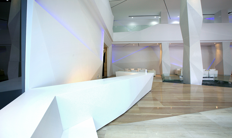 Large, multi-faceted reception desk in Durasein Glacier White solid surface at an airline HQ in Tokyo.