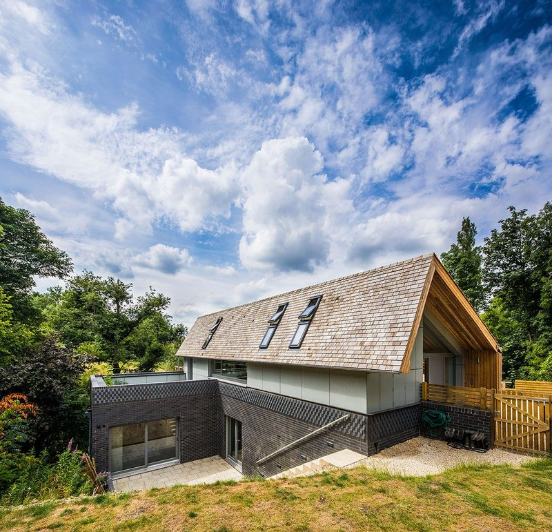 Heavyweight earth-sheltered plinth, highly insulated timber-frame superstructure.