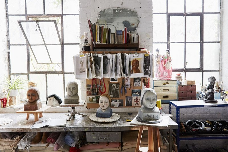 Cathie Pilkington RA's studio. Busts modelled on the doll for Petra confront the viewer with a forthright stare, from the shelves of Ditchling's 'Wunderkammer'.