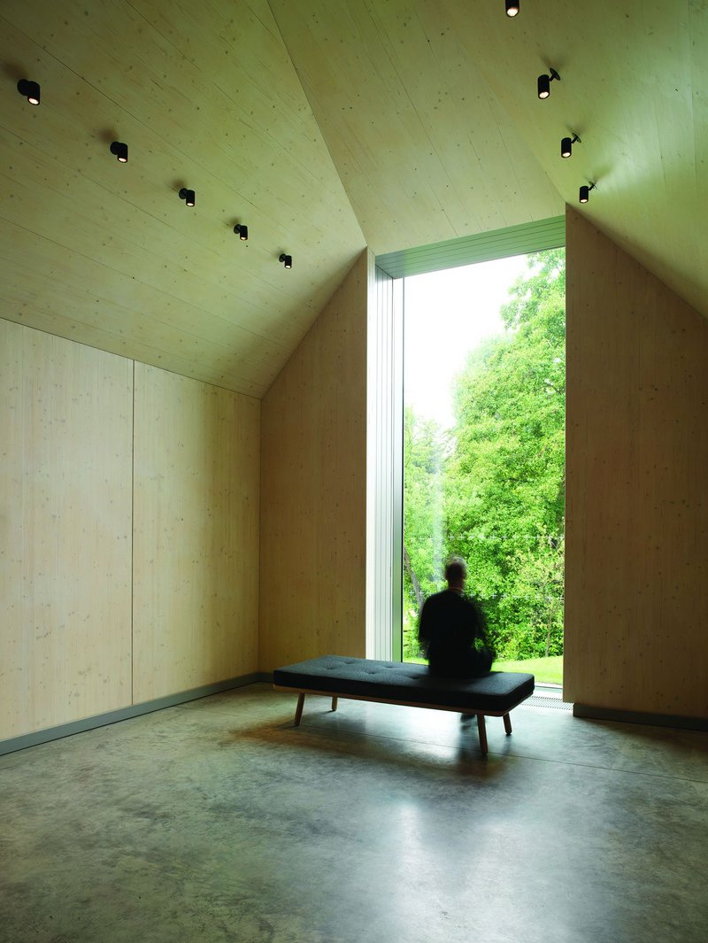 The exposed CLT interior and polished concrete floor lead to a point of contemplation of the verdant setting.