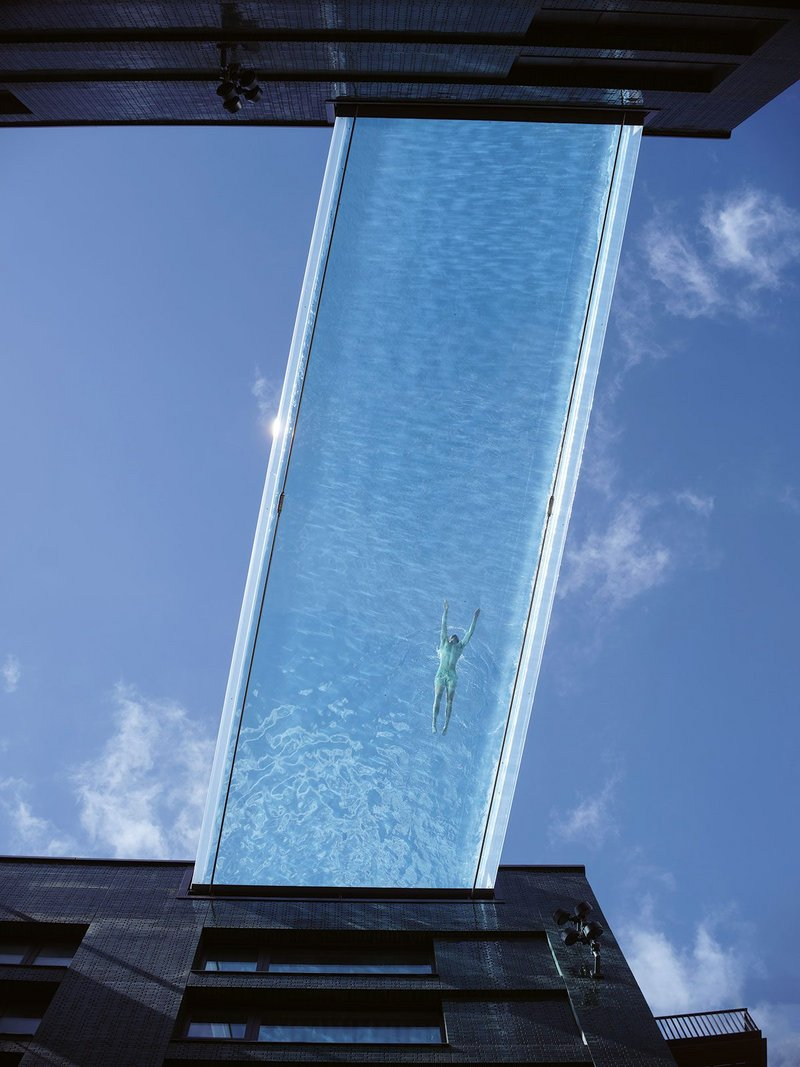The Sky Pool seen from below. The 15m monolithic acrylic structure is clasped to the steel tubs either side by two steel tendons, visible on each side.