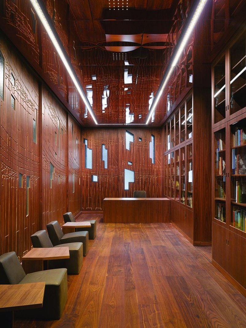 The etching of the exterior cladding is reflected internally in the entrance area. Bespoke shelving and walls suggest a private study, doubled in scale by the mirrored ceiling