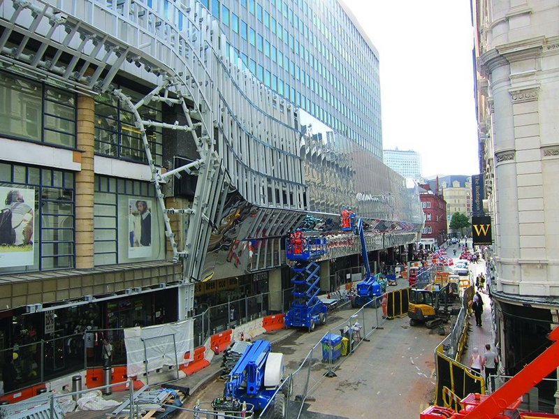 The north facade of Birmingham New St station receiving its mirrored stainless steel appliqué on a secondary steel structure attached directly to the existing concrete structure.