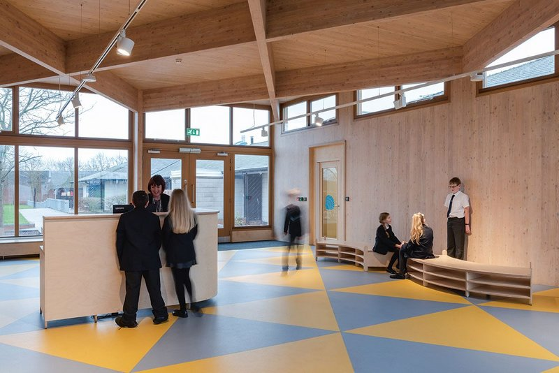 An intriguing entrance to the now-linked two schools with the Infants' in the background. The CLT construction, its geometry reflected in the floor patterning, is designed to be self-explanatory.