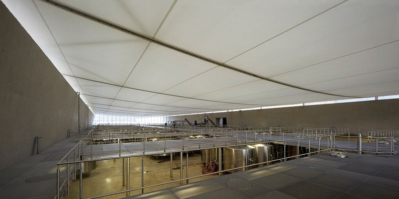 The subtle tensile roof lends simple aesthetic grandeur to this factory floor, and reduces the need for artificial lighting.