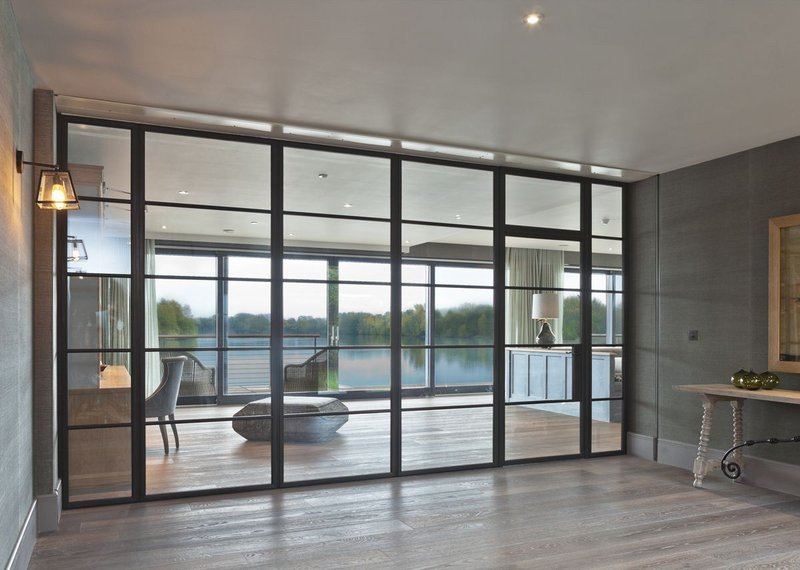 Architectural Bronze Casements' large bronze screen with single Slimline door in a lakeside new-build. Light flows, bringing the view into the hall. Hamilford Design architects.