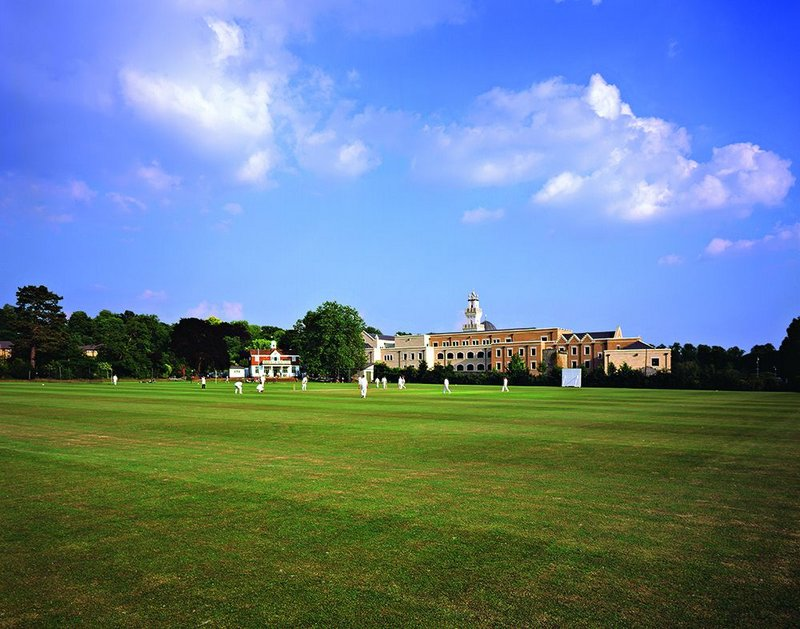 The minaret and dome of the Oxford Centre for Islamic Studies rising from the green pitch of Magdalen College's grounds.