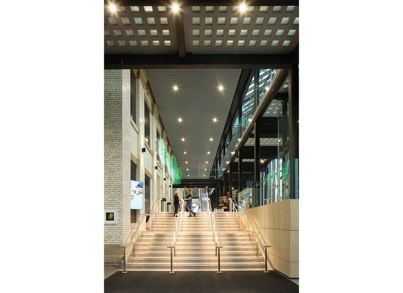 The new cinema concourse. Downlights are minimal, dramatic effects created with narrow beam luminaires on the glazed brick west wall of the town hall and LEDs in the handrails.
